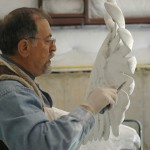 Alex is seen shaping details in the plaster that formed the base for the eagle sculpture.